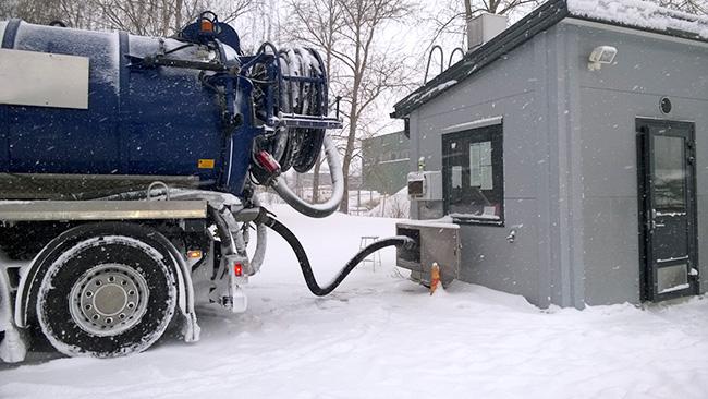 Lietteenkuljetusauto tyhjentää lietettä jätevedenpuhdistamolle. Slamtransportbilen tömmer slam till reningsverket.